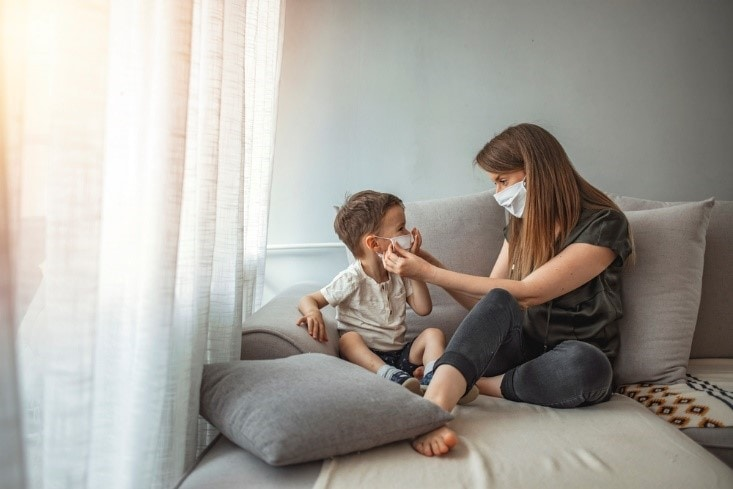 Mother helps a child with autism with wearing a face mask